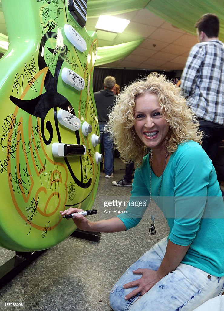 Kimberly Schlapman of Little Big Town signs a giant Patron tequila guitar backstage at the CMA Awards to benefit the 'Keep the Music Playing' music education on November 3, 2013 in Nashville, Tennessee.