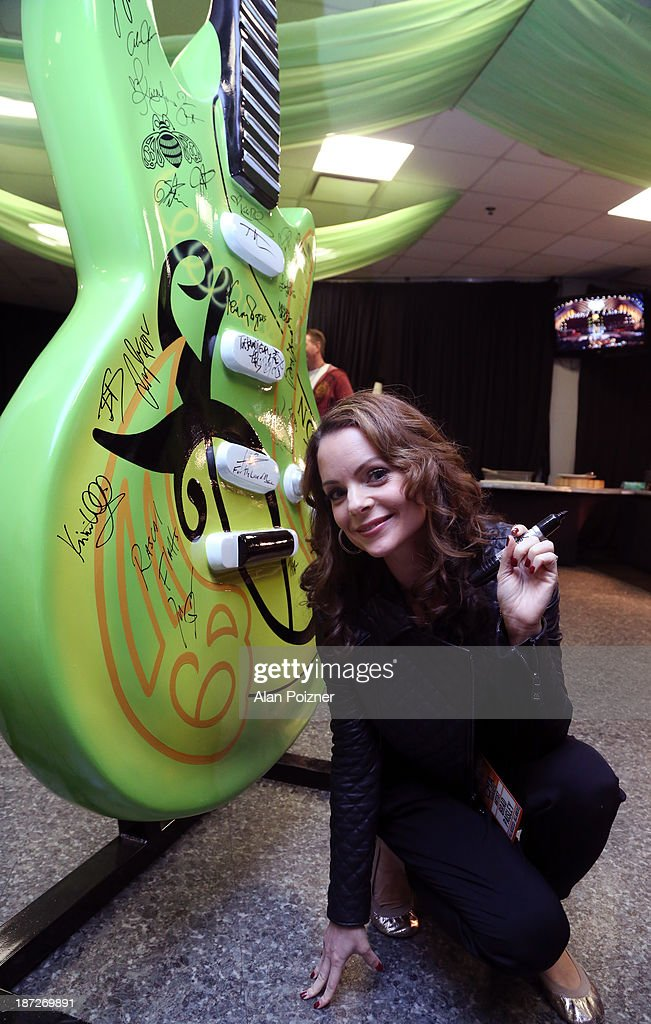 Kimberly Williams-Paisley signs a giant Patron tequila guitar backstage at the CMA Awards to benefit the 'Keep the Music Playing' music education on November 3, 2013 in Nashville, Tennessee.
