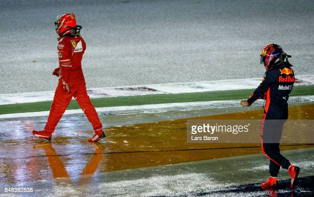 Kimi Raikkonen of Finland and Ferrari and Max Verstappen of Netherlands and Red Bull Racing look dejected after retiring during the Formula One Grand...