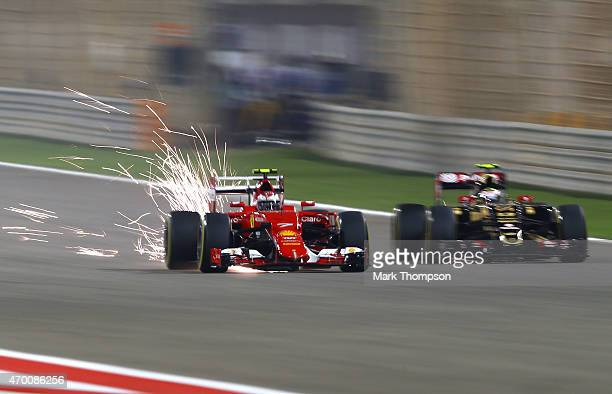 Kimi Raikkonen of Finland and Ferrari and Pastor Maldonado of Venezuela and Lotus drive during practice for the Bahrain Formula One Grand Prix at...