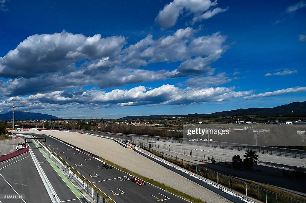 Kimi Raikkonen of Finland and Ferrari drives ahead of Lewis Hamilton of Great Britain and Mercedes GP during day three of F1 winter testing at...