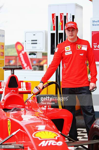 Kimi Raikkonen of Finland and Ferrari fills up an F1 car at a petrol station during a photocall during previews to the Turkish Formula One Grand Prix...