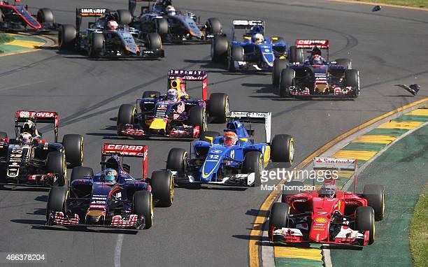 Kimi Raikkonen of Finland and Ferrari runs wide next to Carlos Sainz of Spain and Scuderia Toro Rosso during the Australian Formula One Grand Prix at...