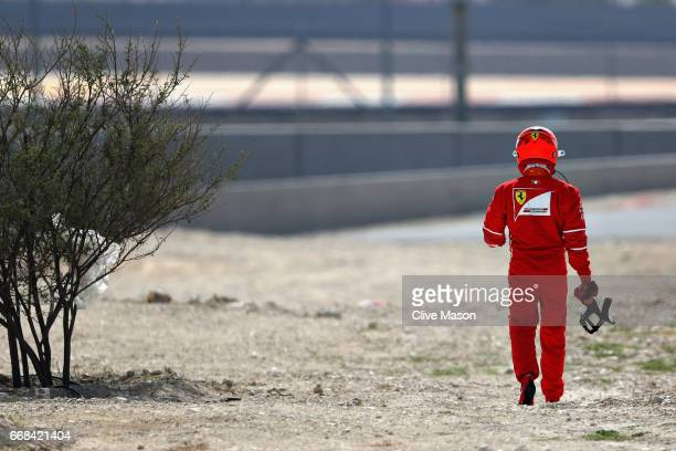 Kimi Raikkonen of Finland and Ferrari walks away after breaking down on track during practice for the Bahrain Formula One Grand Prix at Bahrain...