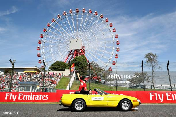 Kimi Raikkonen of Finland and Ferrari waves to the crowd on the drivers parade before the Formula One Grand Prix of Japan at Suzuka Circuit on...