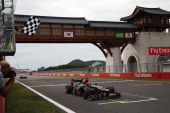 Kimi Raikkonen of Finland and Lotus leads Romain Grosjean of France and Lotus over the line at the finish of the Korean Formula One Grand Prix at...