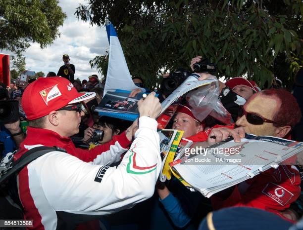 Kimi Raikkonen of Scuderia Ferrari signs autographs ahead of the 2014 Australian Grand Prix at Albert Park Melbourne Australia PRESS ASSOCIATION...