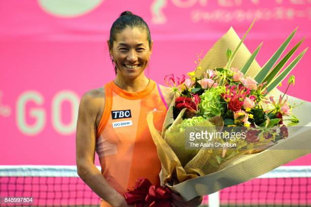 Kimiko Date of Japan poses for photographs during her retirement ceremony after her defeat in the singles first round match against Aleksandra Krunic...