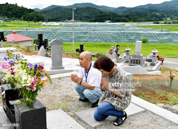 Kimio and Naoko Aoki lay flowers they grew before their family grave while a temporary storage site for radioactive waste generated from...
