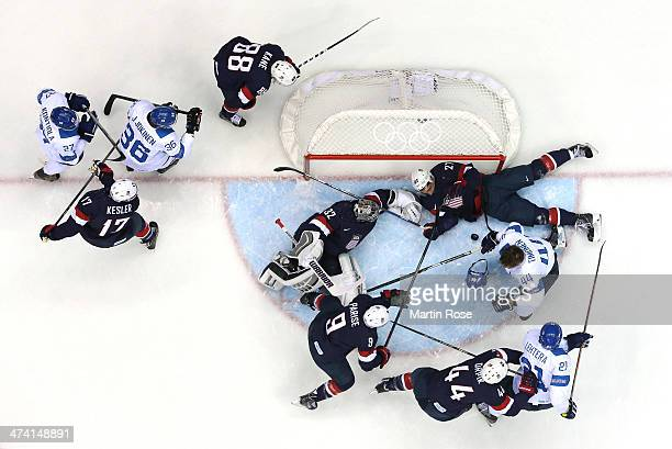 Kimmo Timonen of Finland loses his helmet against Zach Parise Jonathan Quick and Ryan McDonagh of the United States in the first period during the...