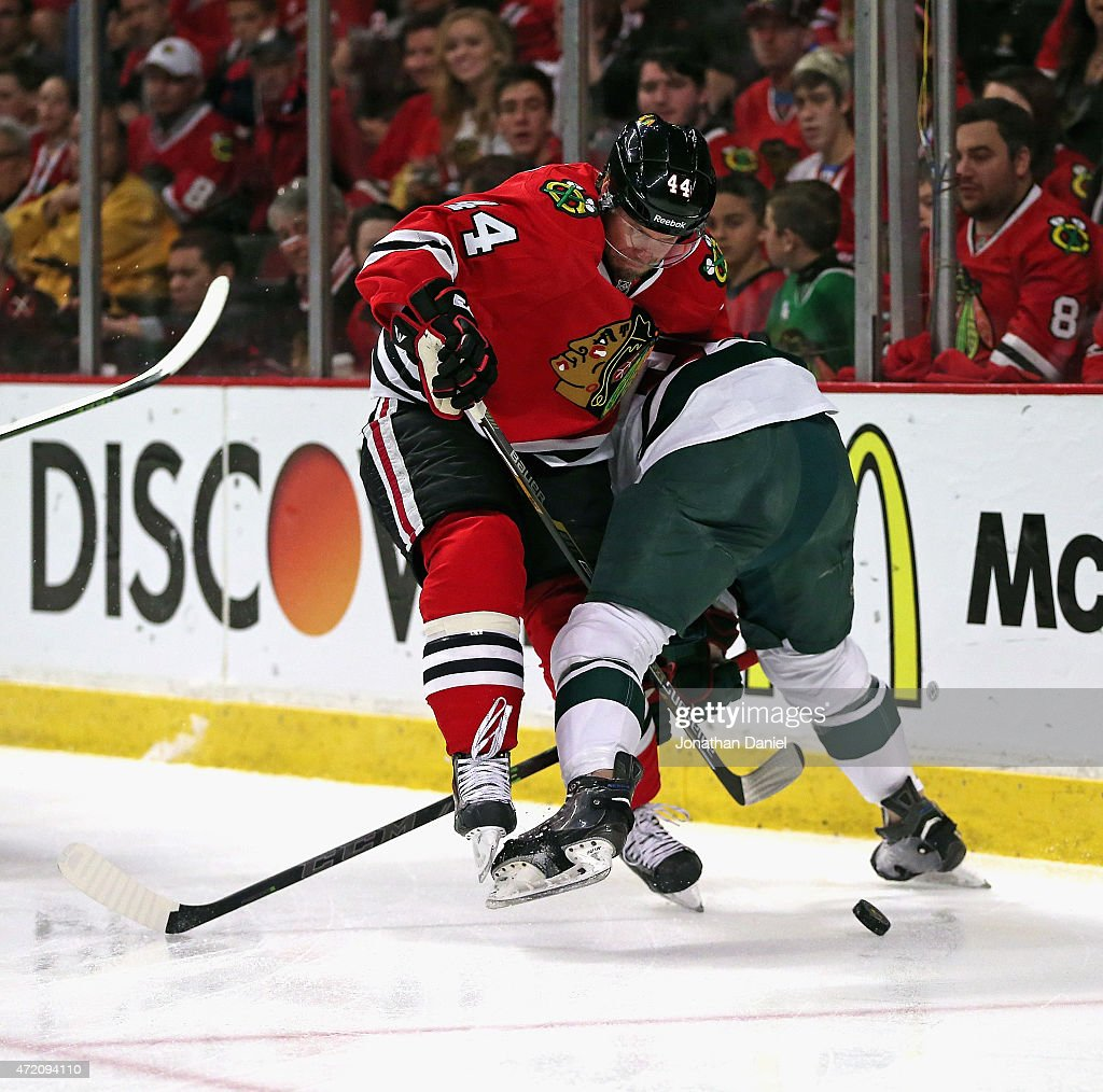 Kimmo Timonen #44 of the Chicago Blackhawks gets tangled up with Erik Haula #56 of the Minnesota Wild as they battle for the puck in Game Two of the Western Conference Semifinals during the 2015 NHL Stanley Cup Playoffs at the United Center on May 1, 2015 in Chicago, Illinois.