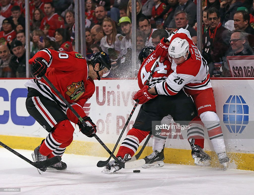 <a gi-track='captionPersonalityLinkClicked' href=/galleries/search?phrase=Kimmo+Timonen&family=editorial&specificpeople=201521 ng-click='$event.stopPropagation()'>Kimmo Timonen</a> #44 of the Chicago Blackhawks pins <a gi-track='captionPersonalityLinkClicked' href=/galleries/search?phrase=Chris+Terry+-+Ice+Hockey+Player&family=editorial&specificpeople=4605771 ng-click='$event.stopPropagation()'>Chris Terry</a> #25 of the Carolina Hurricanes to the boards as <a gi-track='captionPersonalityLinkClicked' href=/galleries/search?phrase=Antoine+Vermette&family=editorial&specificpeople=206302 ng-click='$event.stopPropagation()'>Antoine Vermette</a> #80 digs at the puck at the United Center on March 2, 2015 in Chicago, Illinois.