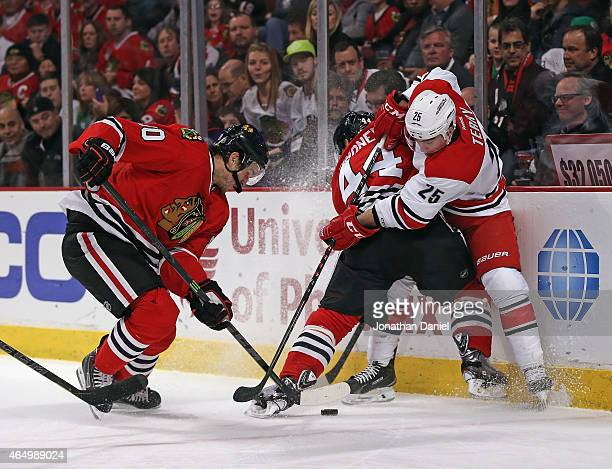 Kimmo Timonen of the Chicago Blackhawks pins Chris Terry of the Carolina Hurricanes to the boards as Antoine Vermette digs at the puck at the United...