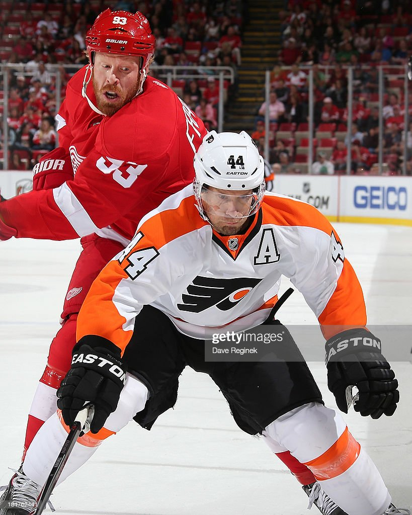 <a gi-track='captionPersonalityLinkClicked' href=/galleries/search?phrase=Kimmo+Timonen&family=editorial&specificpeople=201521 ng-click='$event.stopPropagation()'>Kimmo Timonen</a> #44 of the Philadelphia Flyers and <a gi-track='captionPersonalityLinkClicked' href=/galleries/search?phrase=Johan+Franzen&family=editorial&specificpeople=624356 ng-click='$event.stopPropagation()'>Johan Franzen</a> #93 of the Detroit Red Wings chase the puck during a NHL game at Joe Louis Arena on October 12, 2013 in Detroit, Michigan. The Wings won 5-2