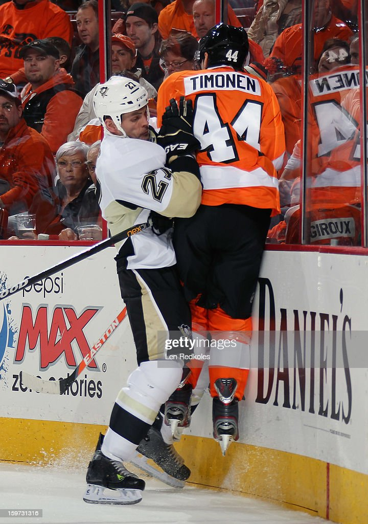 Kimmo Timonen #44 of the Philadelphia Flyers is checked into the boards by Craig Adams #27 of the Pittsburgh Penguins on January 19, 2013 at the Wells Fargo Center in Philadelphia, Pennsylvania.