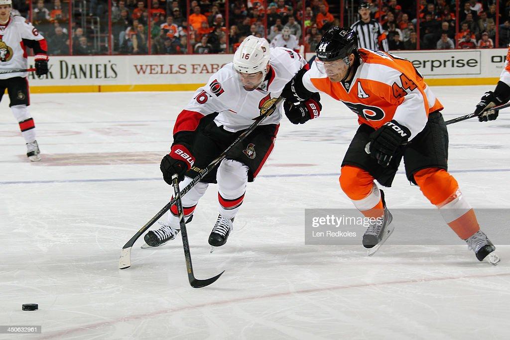 Kimmo Timonen #44 of the Philadelphia Flyers races to reach the loose puck against Clarke MacArthur #16 of the Ottawa Senators on November 19, 2013 at the Wells Fargo Center in Philadelphia, Pennsylvania.