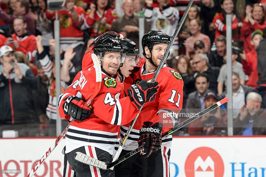 Kimmo Timonen #44, Teuvo Teravainen #86 and Andrew Desjardins #11 of the Chicago Blackhawks celebrate after Teravainen scored against the Vancouver Canucks in the first period during the NHL game at the United Center on April 2, 2015 in Chicago, Illinois.