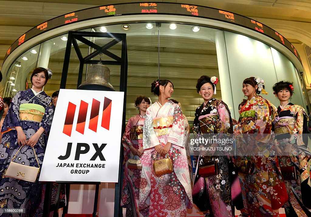 Kimono clad Tokyo Stock Exchange employees smile as the new logo mark of the Japan Exchange Group, Tokyo Stock Exchange and Osaka Stock Exchange which were merged on January 1, is displayed at the opening ceremony of the first trading day of the year at the Tokyo Stock Exchange on January 4, 2013 after the New Year's holidays. Japanese share prices rose 270.92 points to close at 10,666.10 points at the morning session of the Tokyo Stock Exchange, as the yen tumbled on relief over a US deal to avert the 'fiscal cliff' of tax hikes and huge spending cuts. AFP PHOTO / Yoshikazu TSUNO