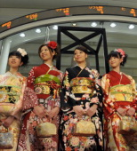 Kimono clad Tokyo Stock Exchange employees smile under the share prices board at the Tokyo Stock Exchange on January 4 2011 at the first trading day...