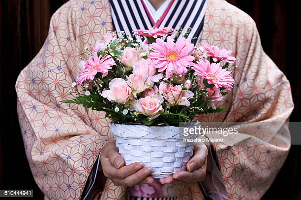 Kimono woman holding flower arrangement