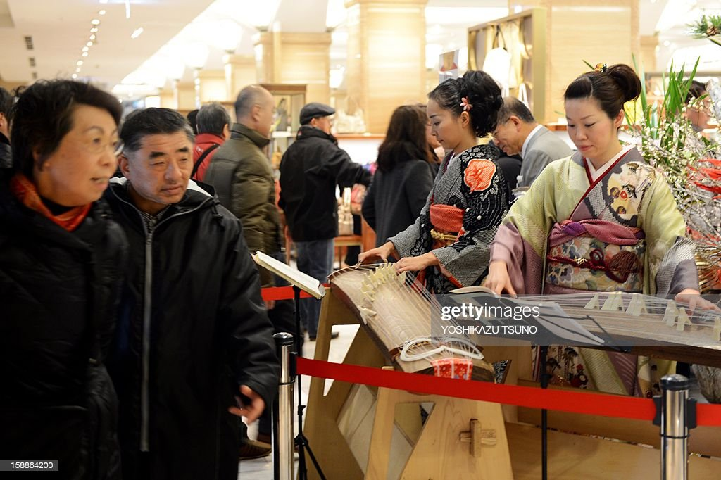 Kimono women play the koto or Japanese harps to greet New Year's shoppers as they rush to pick up 'lucky bags' containing items worth three times as much as their price tag celebrate the New Year's holiday sales at a department store in Tokyo on January 2, 2013. Lucky bags are sold to celebrate the New Year business, Japan's biggest holiday of the year. AFP PHOTO / Yoshikazu TSUNO