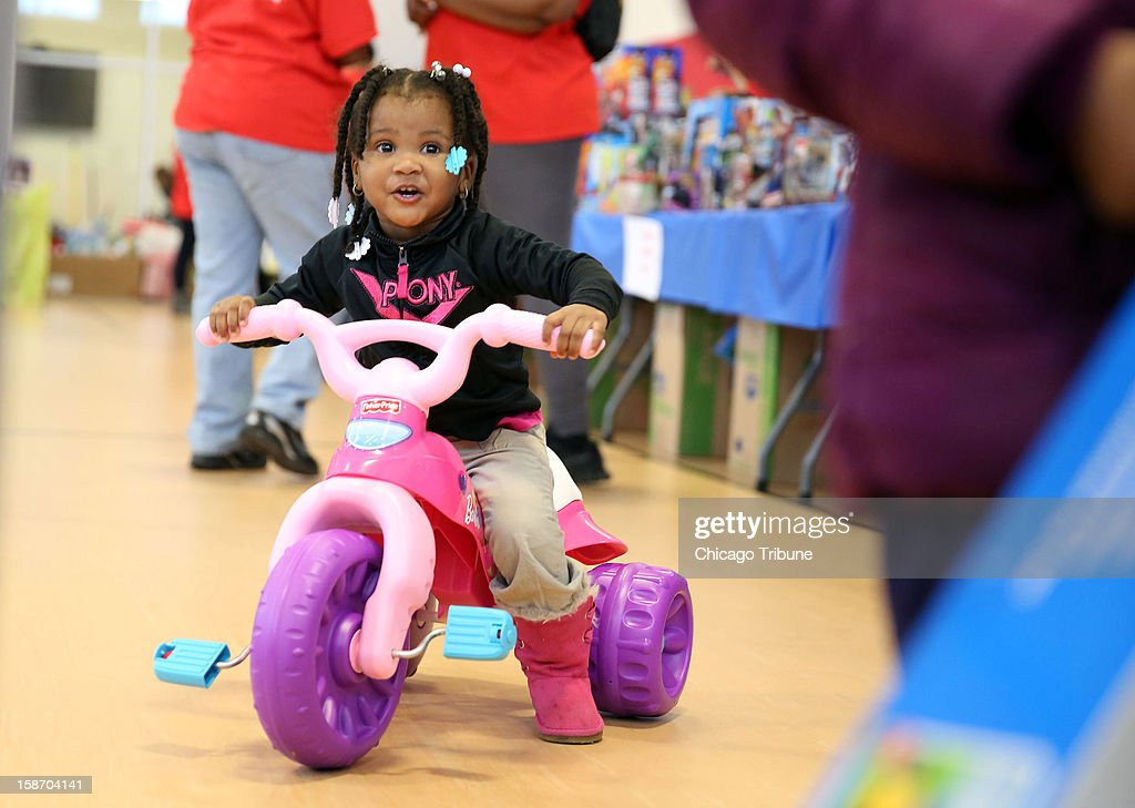 Kimora White, 2, rides a tricycle she picked out during the Julian D. King Gift Foundation Christmas Toy Giveaway at the Ray and Joan Kroc Center in Chicago, Illinois, Monday, December 24, 2012. Jennifer Hudson and her sister, Julia, helped to hand out toys during the event.