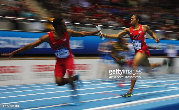 Kind Butler III of the United States passes the baton to Calvin Smith on the way to winning the gold medal in a new indoor world record time in the...