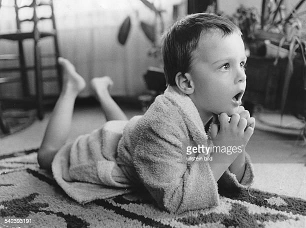 Kind vor dem Fernsehgerät Es liegt im Bademantel auf dem Boden und hat einen staunenden Gesichtsausdruck1972