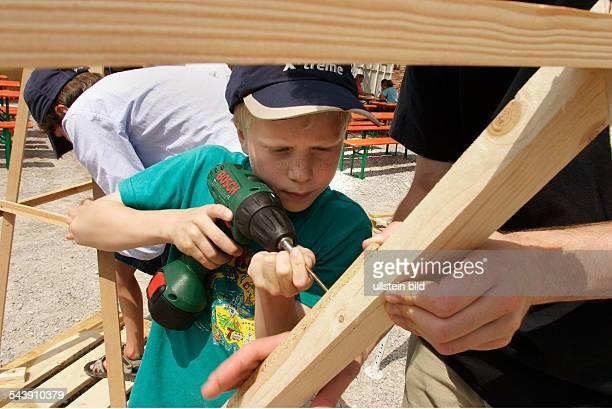 Kinder bauen und basteln Junge schraubt eine Schraube mit einem Akkuschrauber in eine Holzleiste