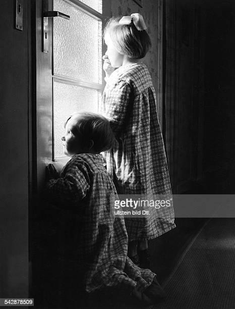 Kinder in Nachthemden blicken durch das Glas einer Tür um das `Christkind` bei seinen weihnachtlichen Vorbereitungen zu erleben Weihnachten 1954