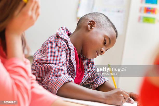 Kindergarten age boy writing on paper in school classroom