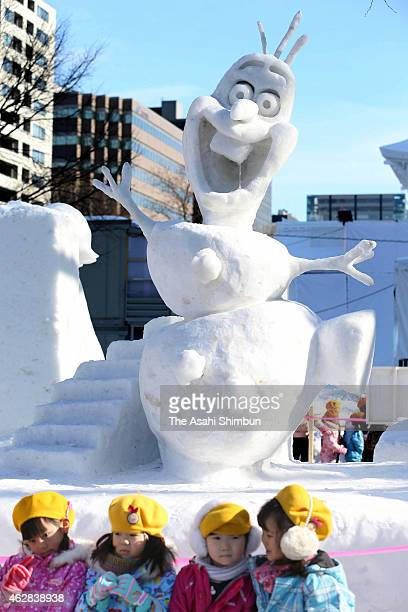 Kindergarten children pose for photographs in front of snow statue of Olaf of the animation movie Frozen is seen during the 66th Sapporo Snow...