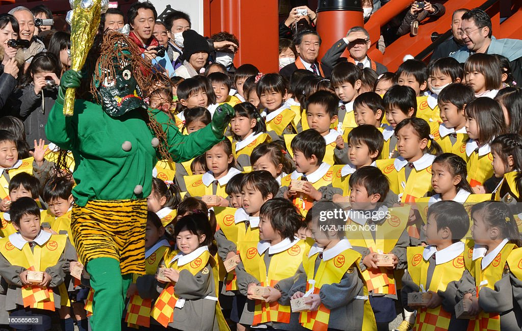 Kindergarten pupils react with their parents, who are wearing demon-like masks to scare the children, during a bean-throwing ceremony to drive away evil and bring good luck at the annual Setsubun Festival at Sensoji Temple in Tokyo on February 3, 2013. Some 370 children attended the festival to greet the coming of spring.
