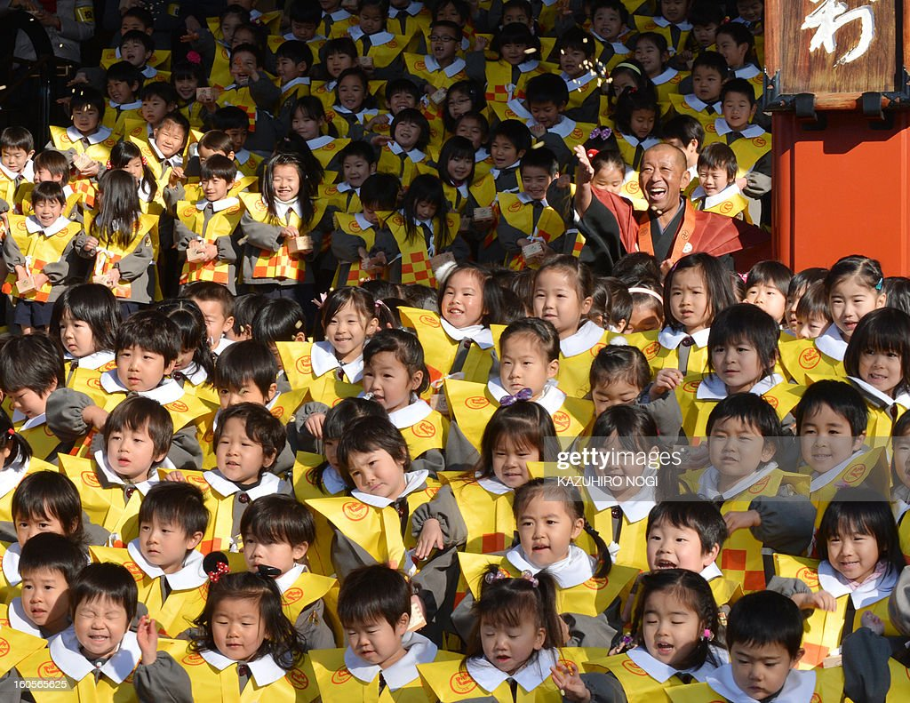 Kindergarten pupils throw beans at their parents (not pictured), who are wearing demon-like masks to scare the children, during a bean-throwing ceremony to drive away evil and bring good luck at the annual Setsubun Festival at Sensoji Temple in Tokyo on February 3, 2013. Some 370 children attended the festival to greet the coming of spring.