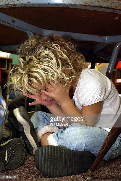 A kindergarten student hides under her desk during a classroom lockdown drill February 18 2003 in Oahu Hawaii Lockdown procedure is used to protect...