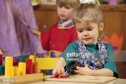Kindergarten student occupied with puzzle : Stock Photo