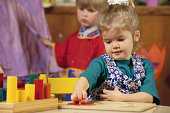 Kindergarten student occupied with puzzle