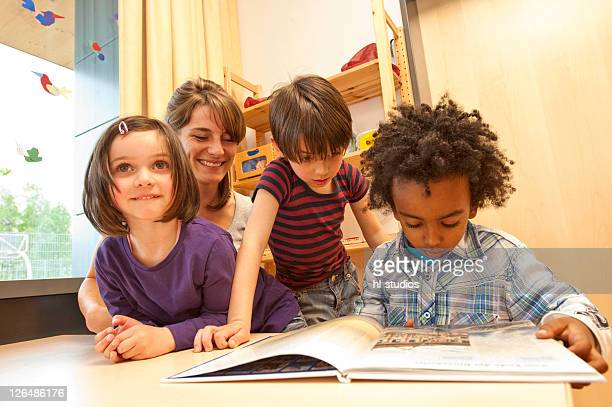 Kindergarten teacher and children looking at a book, low angle view
