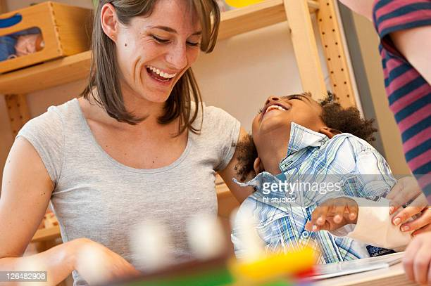 Kindergarten teacher and children looking at book, low angle view