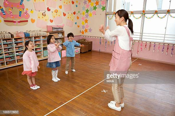 Kindergarten Teacher and Children Playing