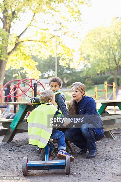 Kindergarten teacher communicating with student on playground