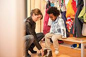 Kindergarten teacher helping boy getting dressed