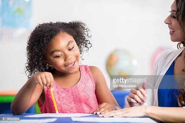 Kindergarten teacher helps student with assignment