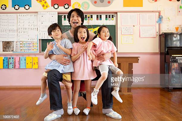 Kindergarten Teacher Holding Children