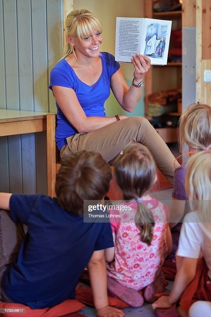 Kindergarten teacher Jennifer Karbot reads a fairy tale about ghosts to her children in a Kindergarten (Kita) on July 11, 2013 in Pfungstadt, Germany. According to numbers which were published by German Family minister Kristina Schroeder, the country reached a family-friendly milestone in boosting the number of child care places. More than 800,000 creche spots for under-three-year-olds would be available in the year starting August 1, surpassing a government target by about 30,000.