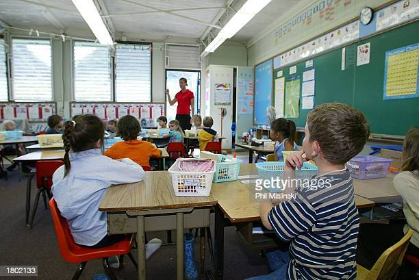 A kindergarten teacher prepares her students for a classroom lockdown drill February 18 2003 in Oahu Hawaii Lockdown procedure is used to protect...