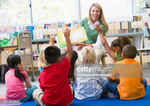 Kindergarten teacher reading to children : Stock Photo