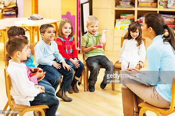 Kindergarten teacher reading to children.