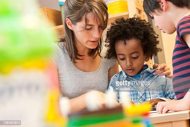 Kindergarten teacher reading with children, low angle view