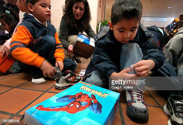 Kindergartner Ernesto SotoBailon joins his classmates in trying on new shoes as students from Barrett Elementary School visit HealthONE Rose Medical...